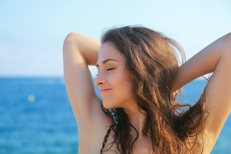 Woman at the seaside with her arms up, Botox for armpit sweating
