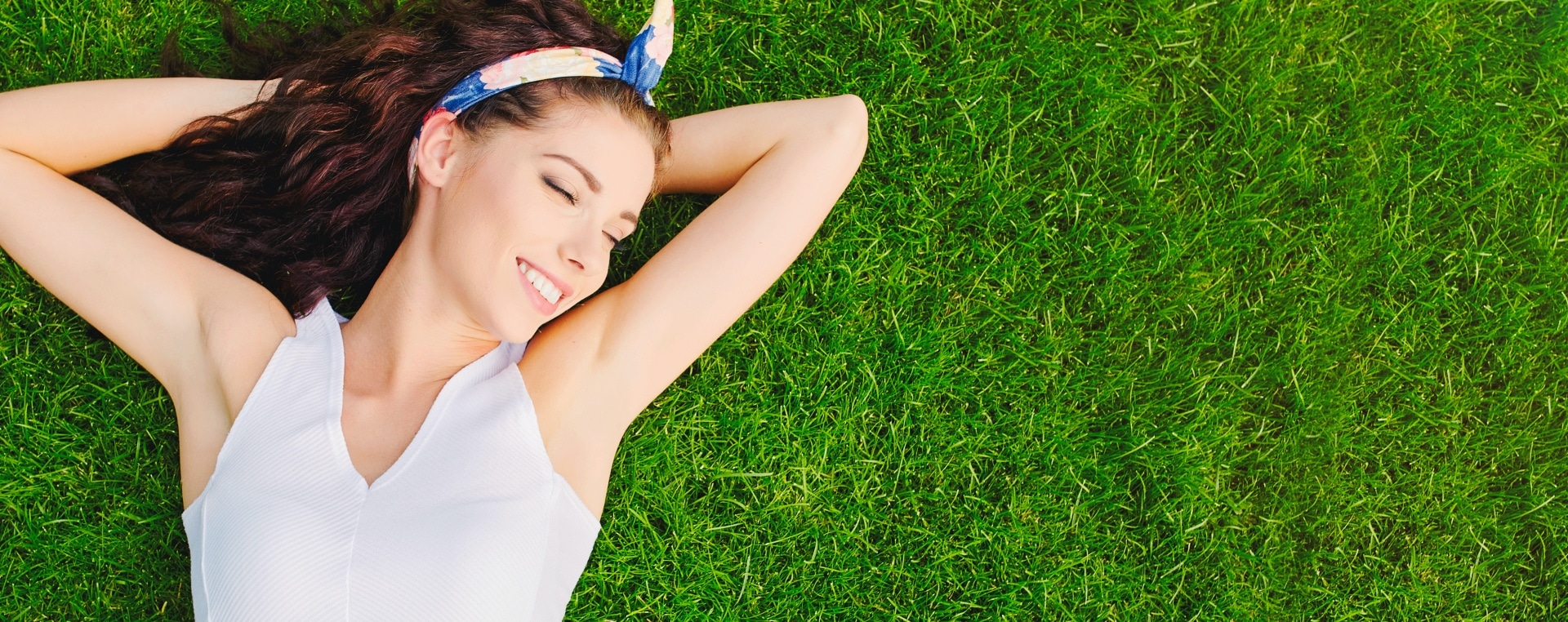 Woman lying on the grass with her arms up