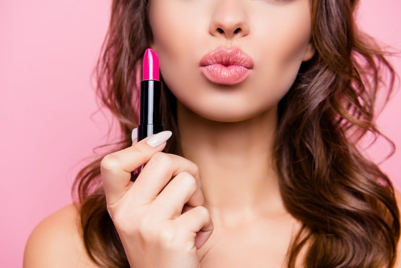 woman pouting and holding a lipstick