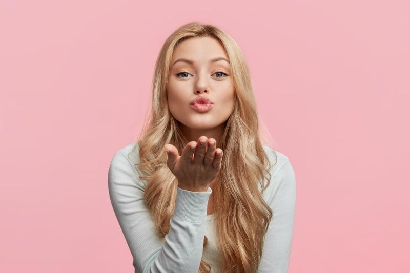 woman blowing a kiss, lip filler aftercare