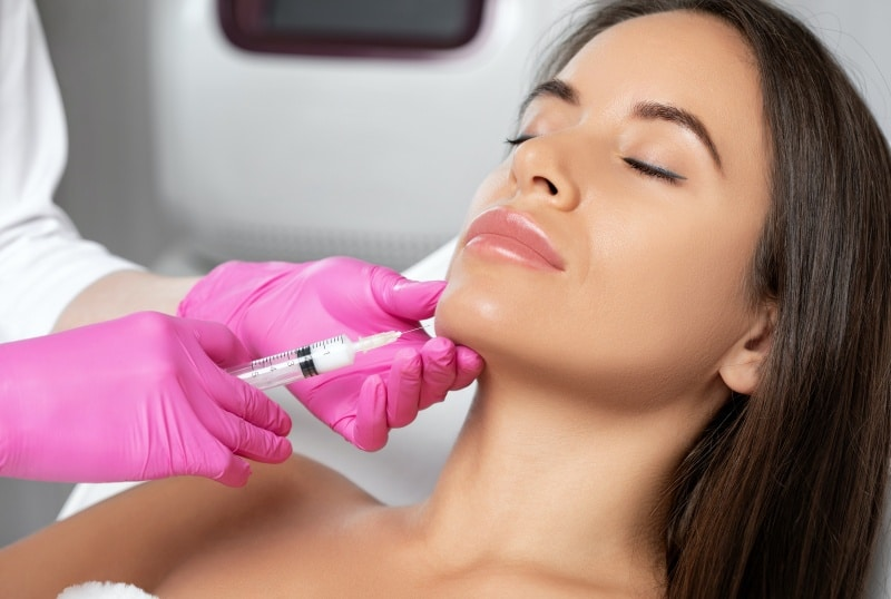 Woman lying while receiving an injection in her jaw, Botox for slimming