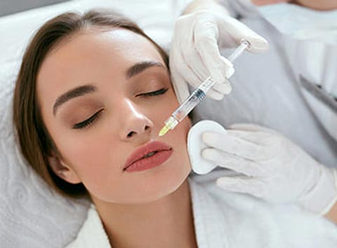 A woman receiving lip filler injectable in her upper lip